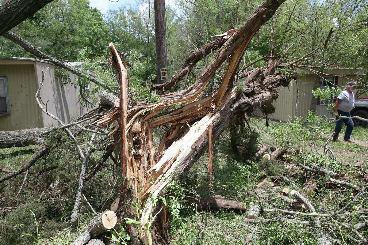 Workers remove shattered tree debris from a mobile home park south of town after storm damage in Kerrville on May 28, 2020.