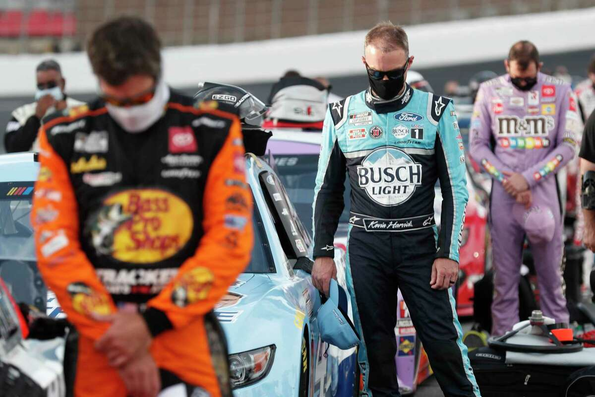 Kevin Harvick, center, prays before a NASCAR Cup Series auto race at Charlotte Motor Speedway Thursday, May 28, 2020, in Concord, N.C. (AP Photo/Gerry Broome)