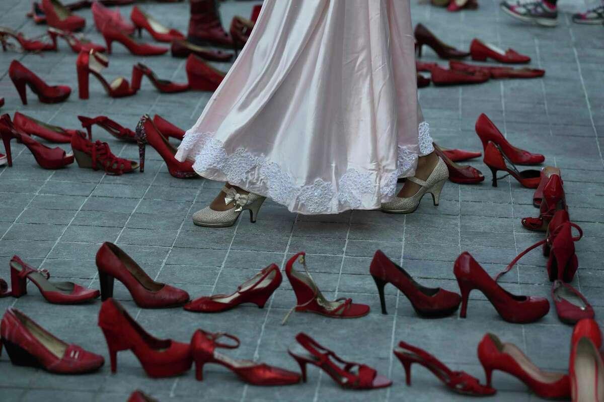 ARCHIVO- Una actriz camina cerca de una línea de zapatos rojos representando a las mujeres asesinadas, como parte de un performance durante la marcha