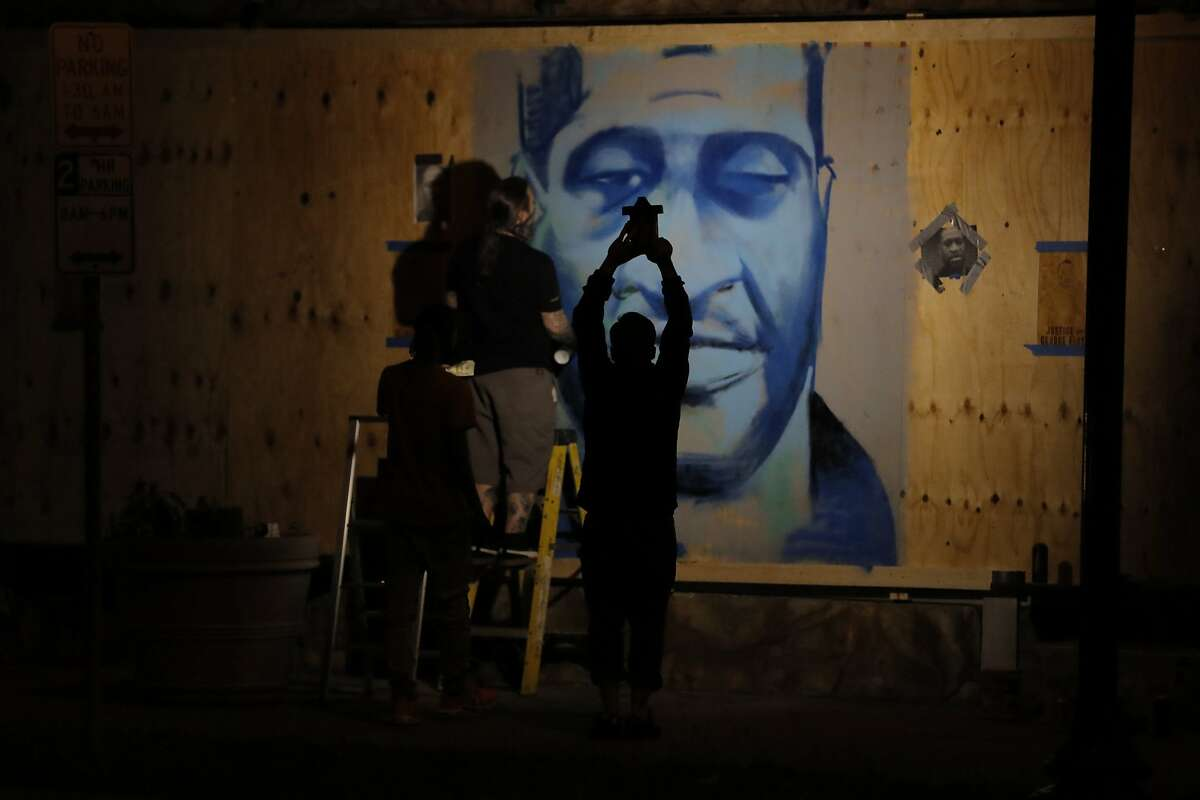 An artist creates an image of George Floyd on Thursday, May 28, 2020, in Minneapolis. Violent protests over the death of Floyd, the black man who died in police custody, broke out in Minneapolis for a third straight night. (AP Photo/Julio Cortez)