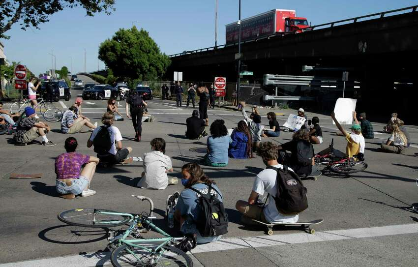 Protestors block an intersection outside the Oakland police department on Thursday, May 28, 2020, in Oakland, Calif.