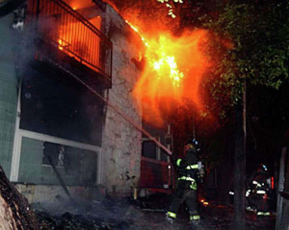 A firefighter shoots water at a blaze at the Arbor Hill Apartments near Heimer Road and Bitters shortly before midnight.