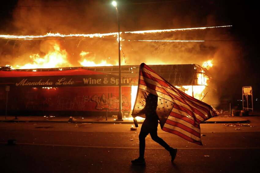 A protester carries a U.S. flag upside, a sign of distress, next to a burning building Thursday, May 28, 2020, in Minneapolis. Protests over the death of George Floyd, a black man who died in police custody Monday, broke out in Minneapolis for a third straight night.