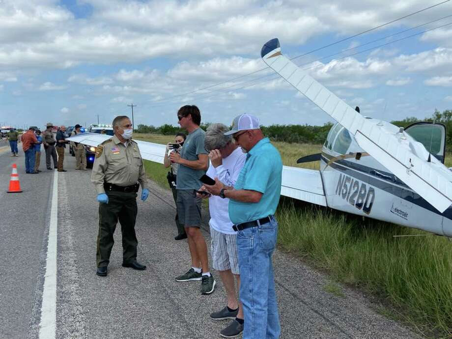 Webb County Sheriff Martin Cuellar speaks to the three occupants of a small private plane that had an emergency landing on U.S. 59, east of Laredo. Photo: Courtesy Photo /Webb County Sheriff's Office