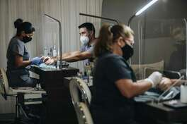 Nail technicians are protected by plexiglass barriers while working on customers' nails at a salon in Coral Gables, Florida, on May 18, 2020.