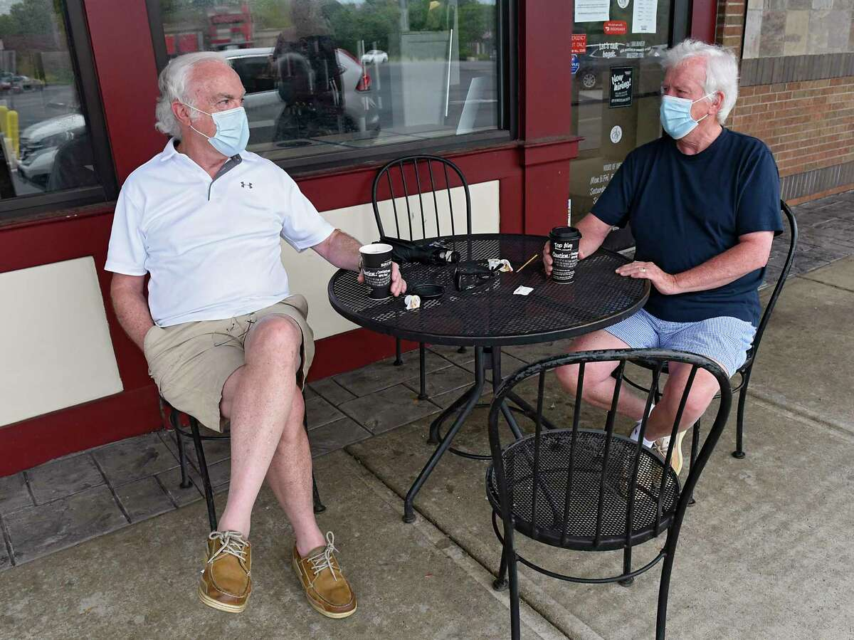 Tom Quinlivan of Albany chats with his friend Art Moseley of Albany over a cup of coffee outside of Bruegger's at Stuyvesant Plaza on Friday, May 29, 2020 in Guilderland, N.Y. (Lori Van Buren/Times Union)