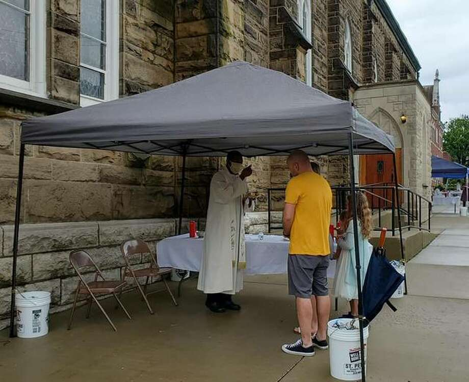 Fr. Benjamin Unachukwu OMV gives Holy Communion to a parish family outside of St. Mary's Catholic Church in Alton on Sunday, May 17. Gov. J.B. Pritzker announced Thursday that Illinois residents can now attend worship services without fear of prosecution. Bishop Thomas John Paprocki of The Diocese of Springfield has granted permission for public Masses to be celebrated in the diocese as soon as the weekend of June 6-7.