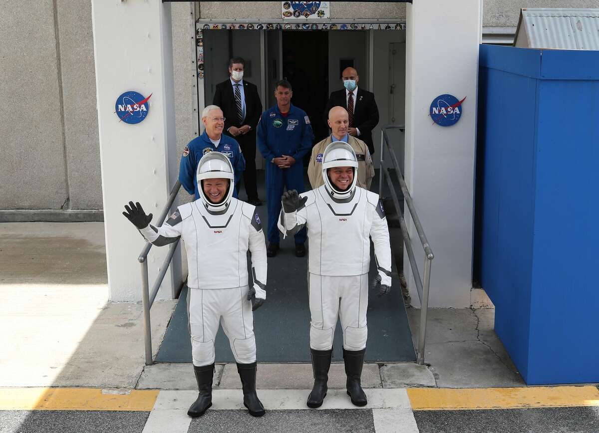 NASA astronauts Bob Behnken (R) and Doug Hurley (L) walk out of the Operations and Checkout Building on their way to the SpaceX Falcon 9 rocket with the Crew Dragon spacecraft on Launch Complex 39A at the Kennedy Space Center on May 27, 2020. (Photo by Joe Raedle/Getty Images)