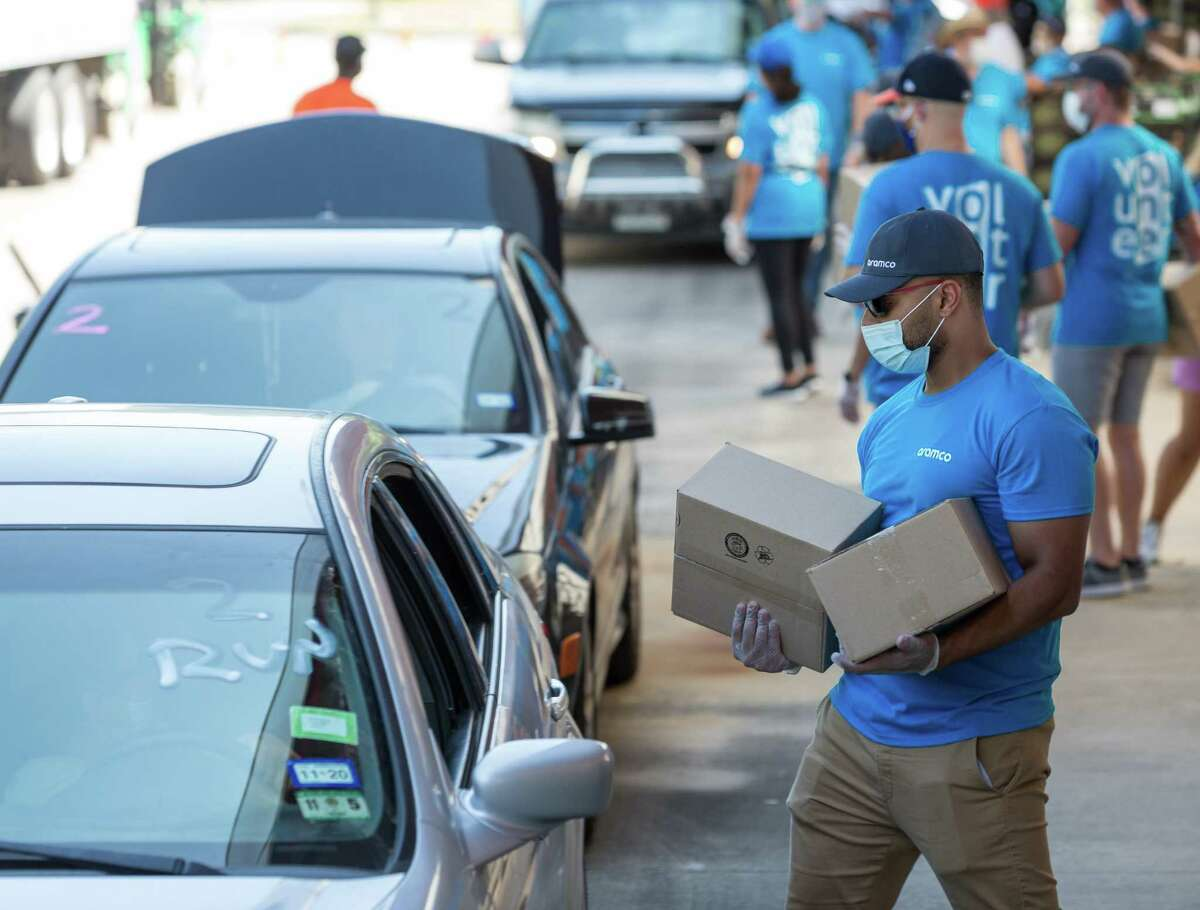 Aramco Americas volunteer Fahad Jabry places food in a vehicle at a Houston Food Bank distribution point serving northwest Houston.