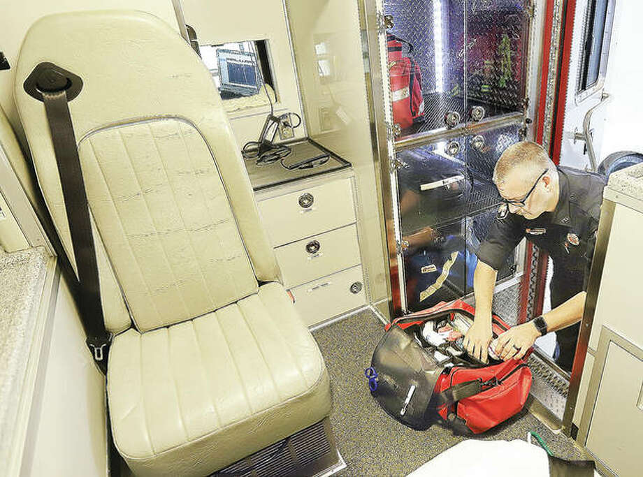 Edwardsville Fire Department paramedic Derek Huber checks equipment in his ambulance near the start of a shift. Huber also is a firefightrer for the department and its infectious disease coordinator.