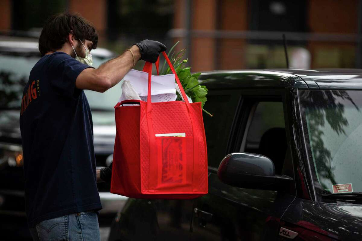 People deliver bags of Pearl Farmers Market items to vehicles during pick-up for online ordering at the Pearl. The popular curbside program will continue.