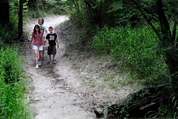 Amy Hoke, Horton Hoke, and Matthew Hoke hike one of the trails at Village Creek Park in Lumberton, Wednesday. Tammy McKinley/The Enterprise