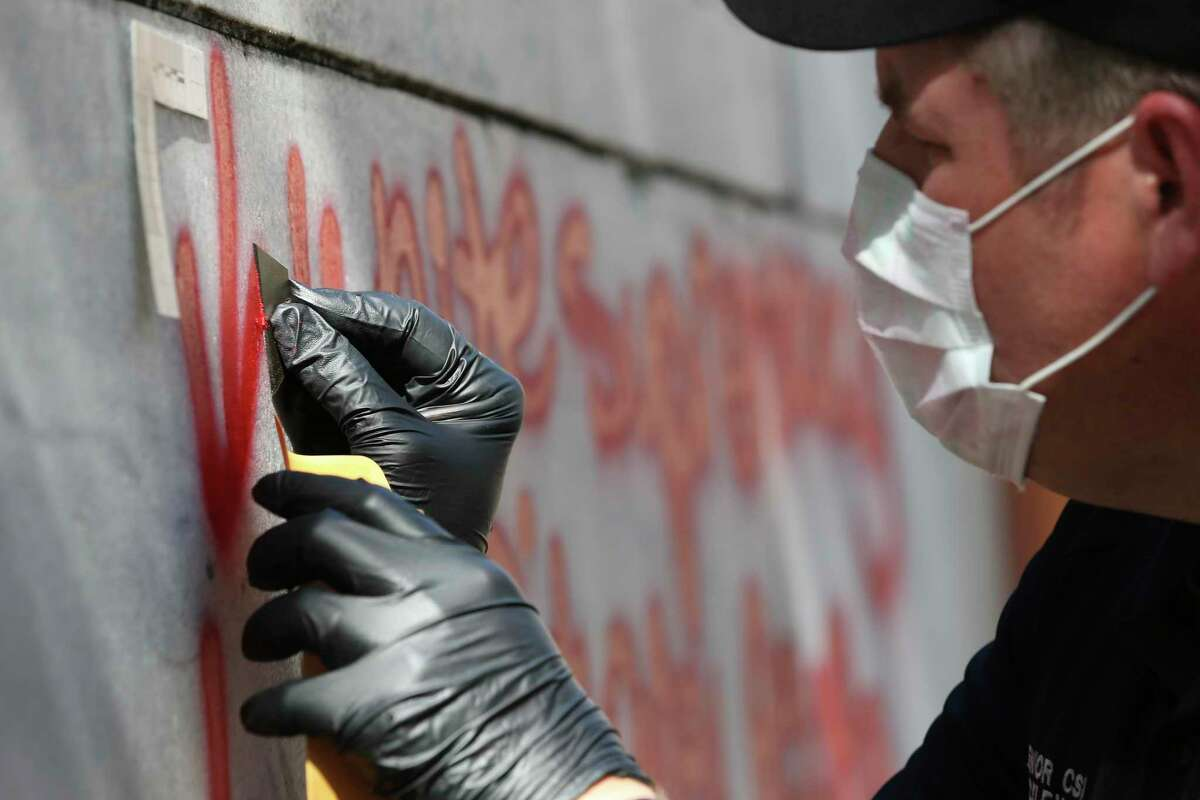 San Antonio Police Senior CSI Robert Rackley carefully scrapes a sample of red paint from the Cenotaph early Friday.
