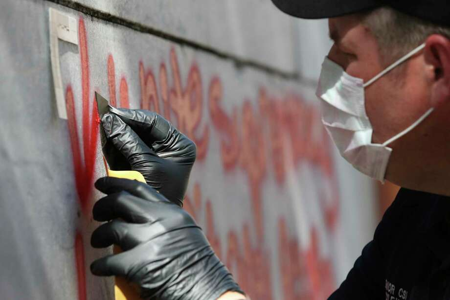 San Antonio Police Senior CSI Robert Rackley carefully scrapes a sample of red paint from the Cenotaph early Friday. Photo: Jerry Lara /San Antonio Express-News / **MANDATORY CREDIT FOR PHOTOG AND SAN ANTONIO EXPRESS-NEWS/NO SALES/MAGS OUT/TV   © 2019 San Antonio Express-News