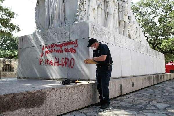 San Antonio Police Senior Crime Scene Investigator Robert Rackley takes evidence of graffiti on the Alamo Cenotaph, Friday, May 29, 2020.
