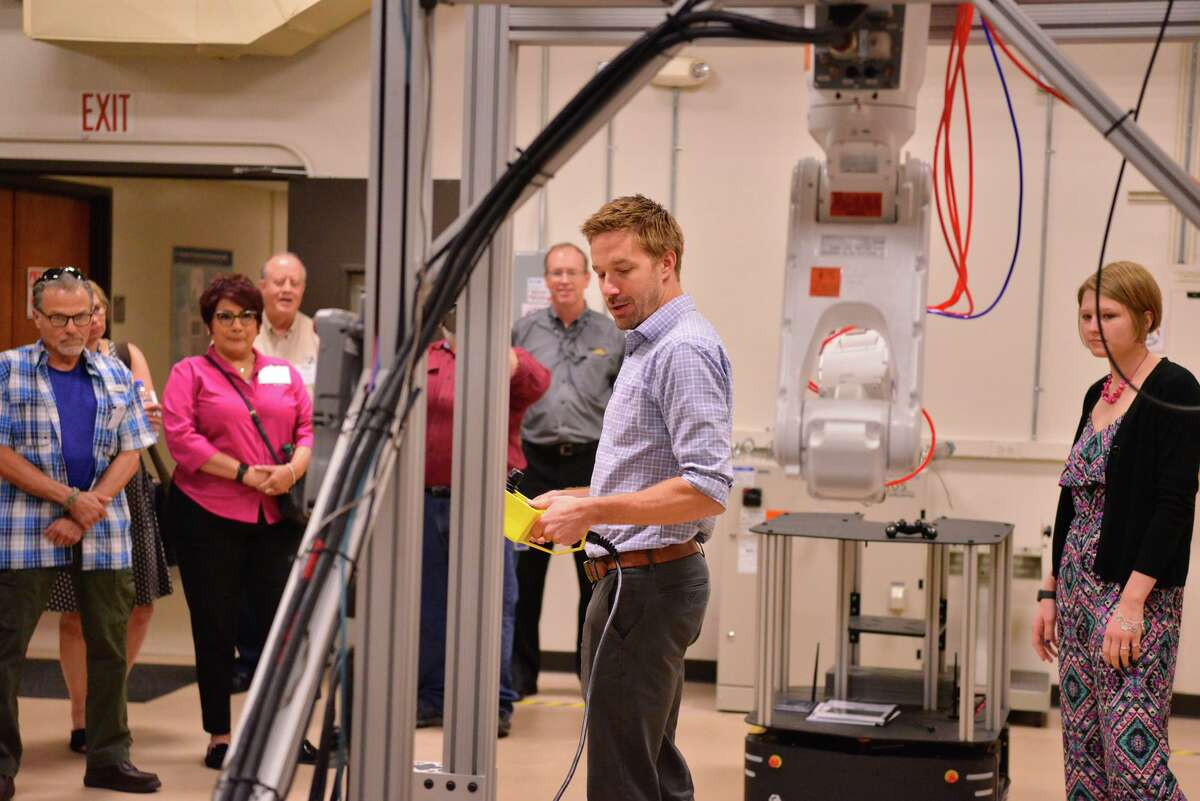 Cody Porter describes an omni-directional platform during a tour at the Southwest Research Institute last yeary for people involved in manufacturing. The institute jumped on the hunt for a COVID-19 treatment as soon as the virus' protein was published in February.