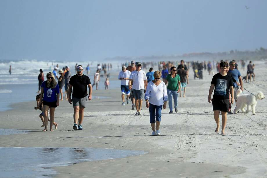 People are seen at the beach on April 17, 2020, in Jacksonville Beach, Fla., after social distancing restrictions were partially eased. (Sam Greenwood/Getty Images/TNS) Photo: Sam Greenwood / TNS / Getty Images North America