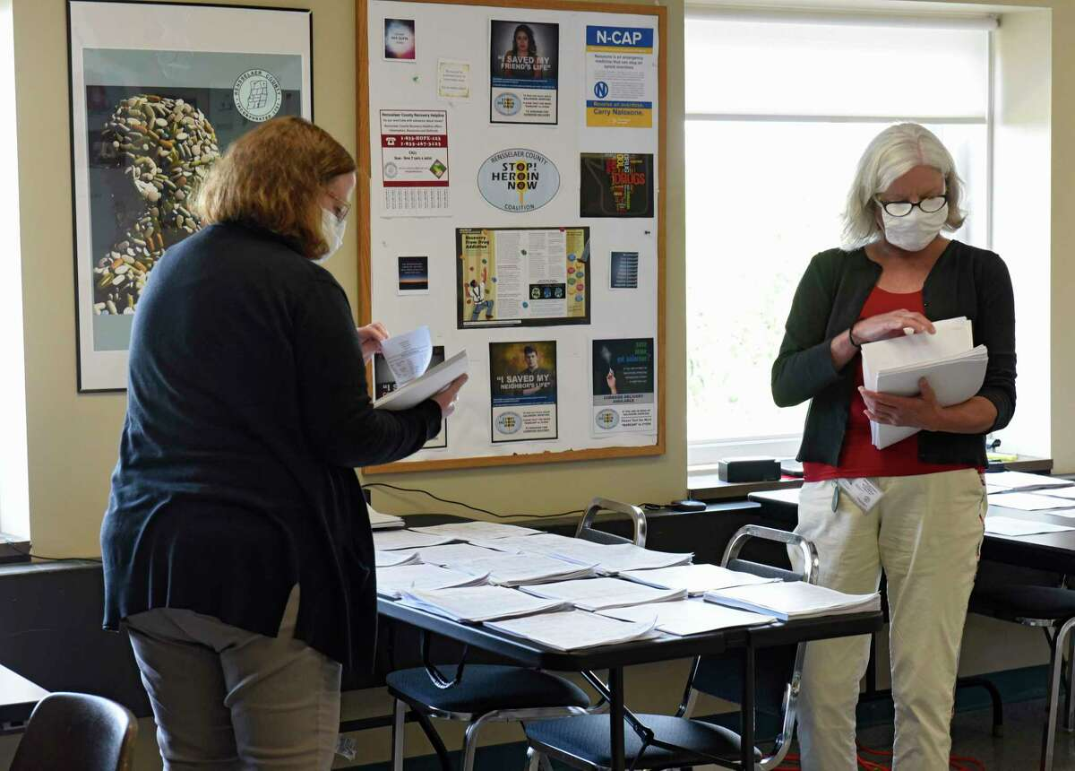 Rensselaer County contact tracers Beverly Falquez, left, and Terri Jackson sort out forms as they work on tracking people down who have been exposed to COVID-19 at the Rensselaer County Office Building on Friday, May 29, 2020 in Troy, N.Y. (Lori Van Buren/Times Union)
