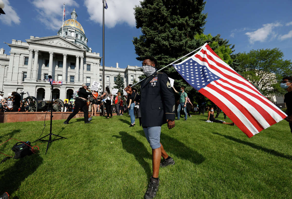 Aubrey Rose, who earned the rank of staff sergeant while serving four tours of duty in the U.S. Army, carries a flag during a protest outside the State Capitol over the death of George Floyd, a handcuffed black man in police custody in Minneapolis, Thursday, May 28, 2020, in Denver. Close to 1,000 protesters walked from the Capitol down the 16th Street pedestrian mall during the protest.