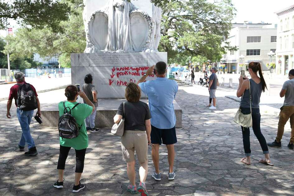 People photograph and watch graffiti on the Alamo Cenotaph, Friday, May 29, 2020.