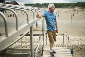 Bill Huss looks out from his dock across what was once a full Sanford Lake and is now a barren, muddy expanse, Thursday, May 28, 2020 in Sanford. (Katy Kildee/kkildee@mdn.net)