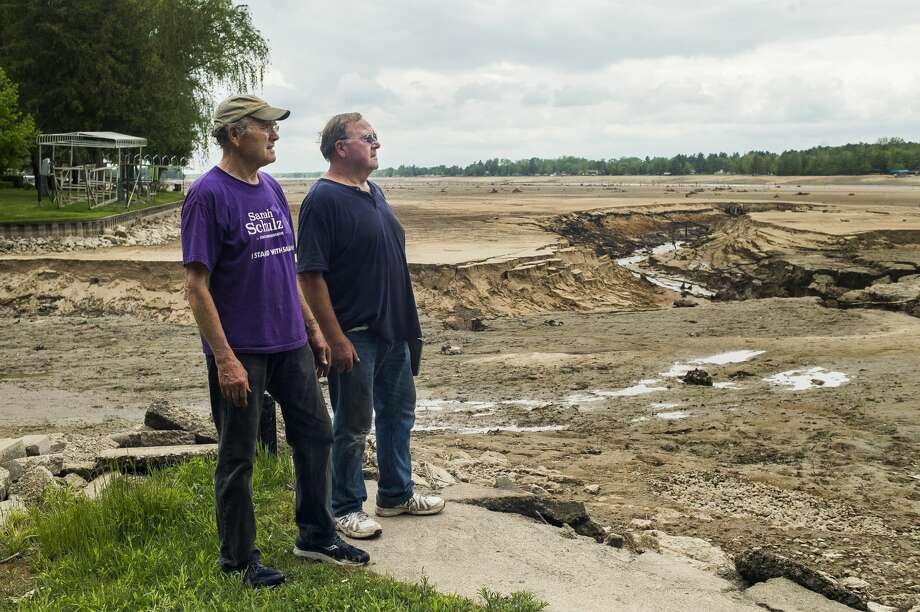 FILE — John McPeak, left, and Eric McPeak, right, look out across the muddy surface of Wixom Lake from their family's lakefront property Thursday, May 28, 2020 in Hope. (Katy Kildee/kkildee@mdn.net) Photo: (Katy Kildee/kkildee@mdn.net)
