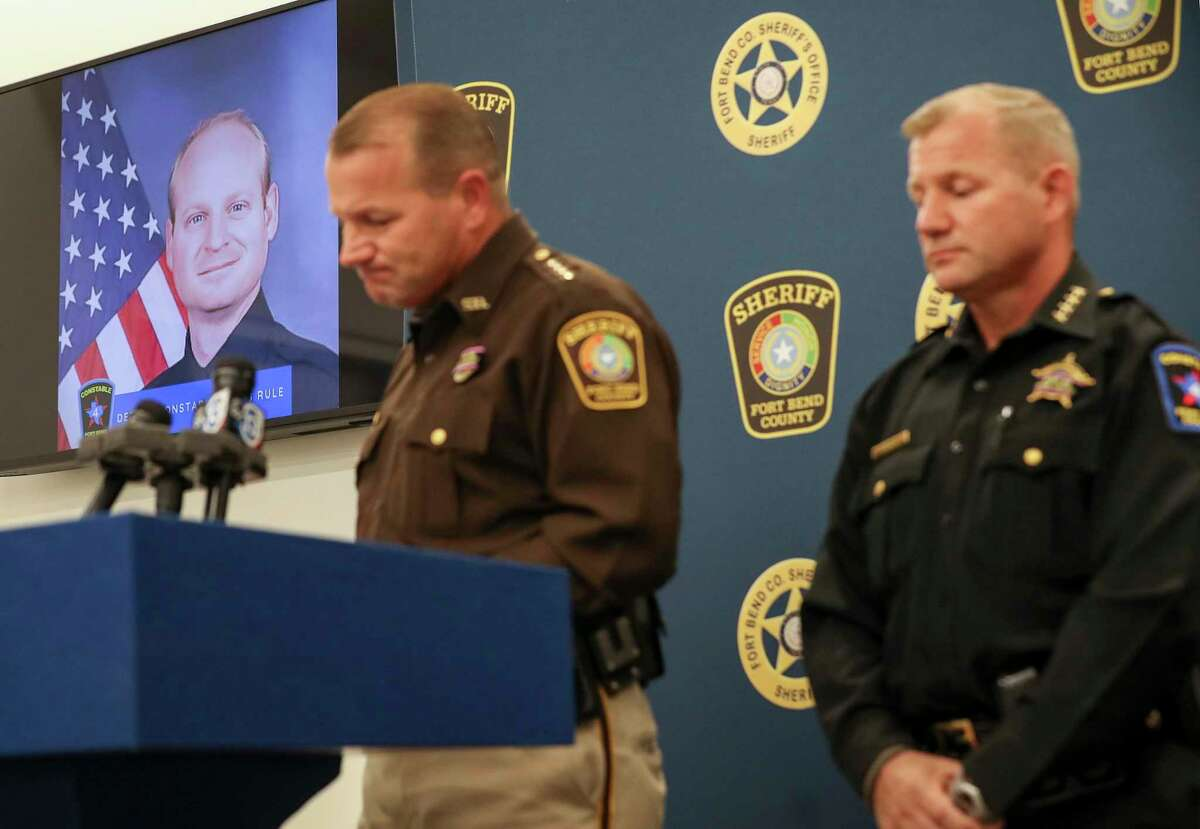 A photo of Fort Bend County Precinct 4 Deputy Constable Caleb Rule, left, is seen as Fort Bend County Sheriff Troy Nehls, center, and his brother Fort Bend County Precinct 4 Constable Trever Nehls speak during a press conference Friday, May 29, 2020, in Richmond. Earlier in the morning, a Fort Bend County Deputy Sheriff fatally shot Rule after mistaking him for an intruder as they cleared a house in nearby Missouri City. Rule was flown to Memorial Hermann hospital, but he did not survive.