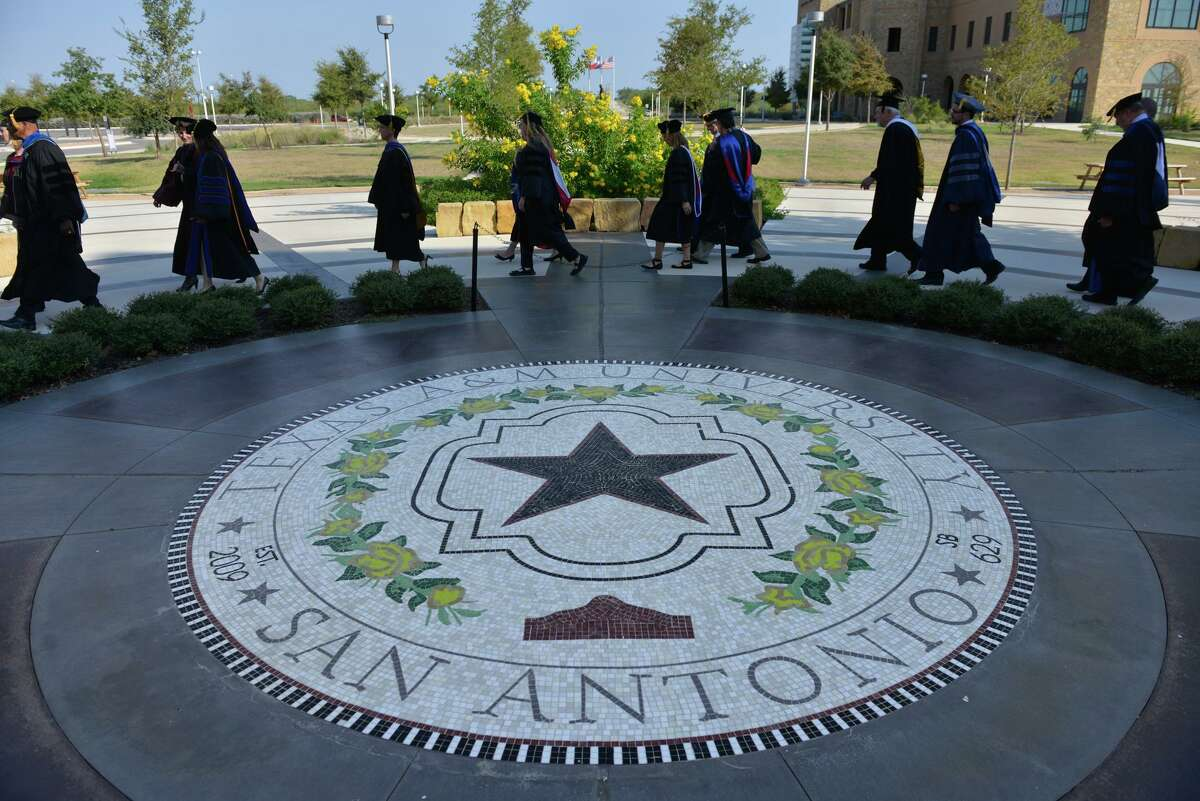 Faculty members of Texas A&M San Antonio pass the seal of the university on their way to the inauguration of the school's new president, Cynthia Teniente-Matson, in 2019.