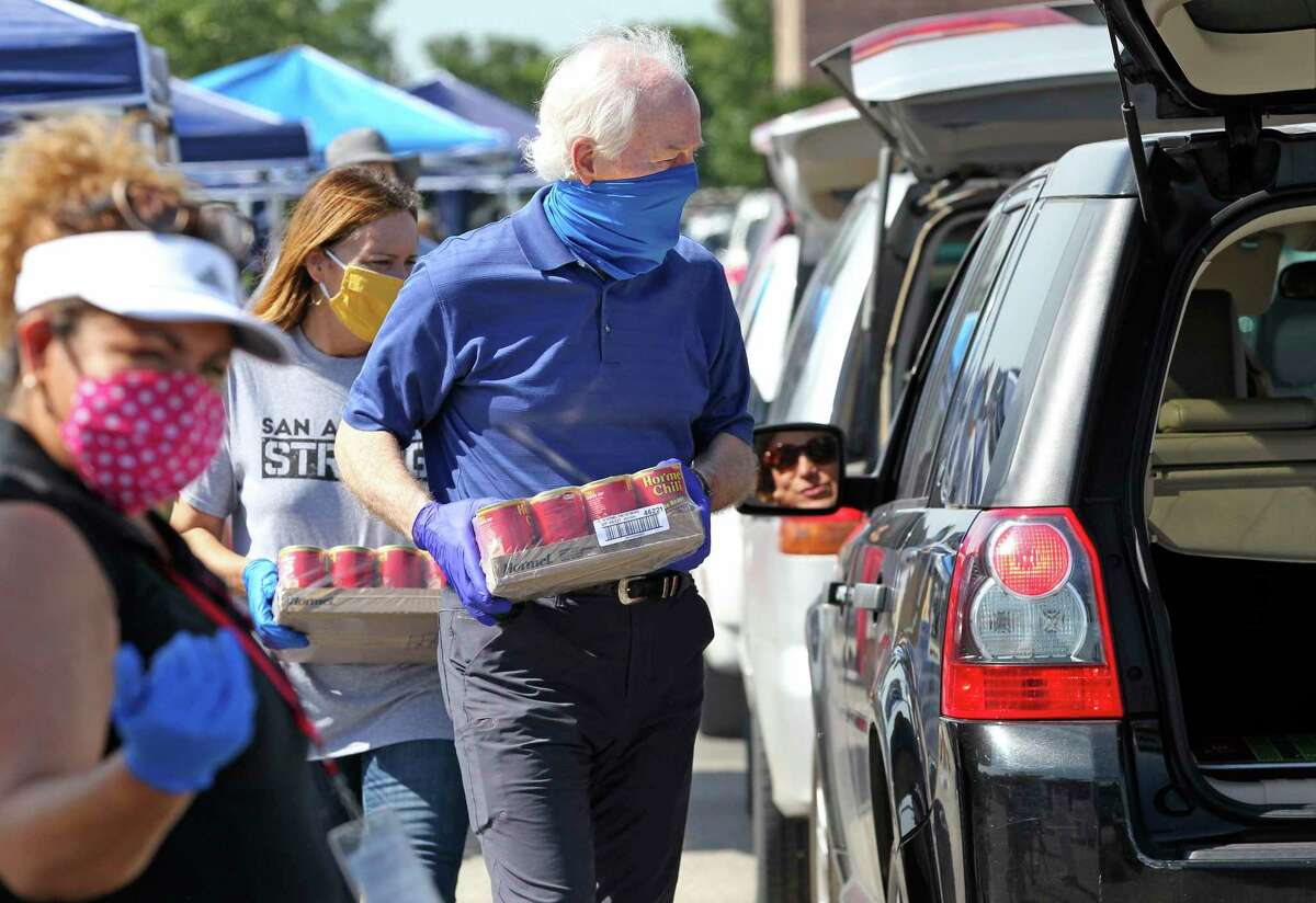 U.S. Sen. John Cornyn chats with a driver as he prepares to load a case of canned soup into the vehicle during a food distribution event organizd by the San Antonio Food Bank at the Alamodome on May 29, 2020.