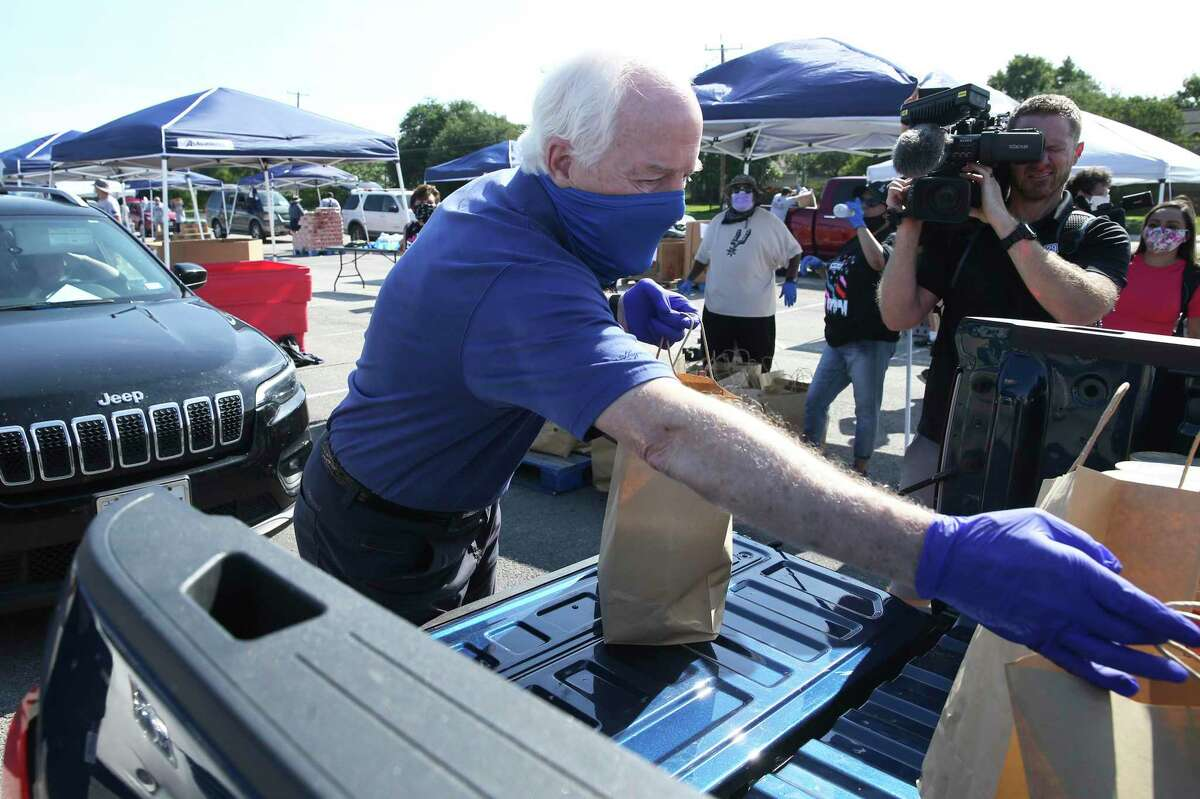 U.S. Sen, John Cornyn helps load bags of groceries into a truck during a food distribution event organized by the San Antonio Food Bank at the Alamodome on Friday, May 29, 2020.
