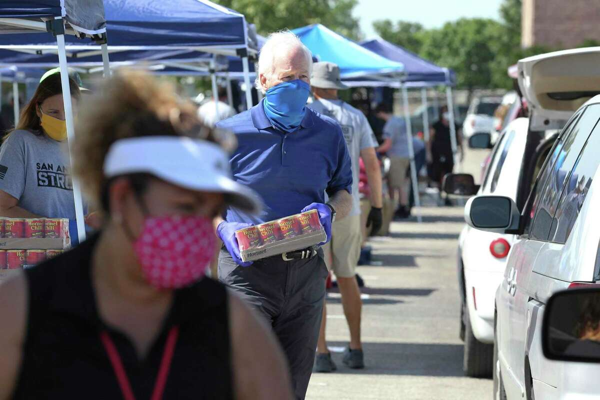 U.S. Sen. John Cornyn carries a case of canned soup as he helps the Food Bank distribute groceries at the Alamodome on Friday, May 29, 2020.