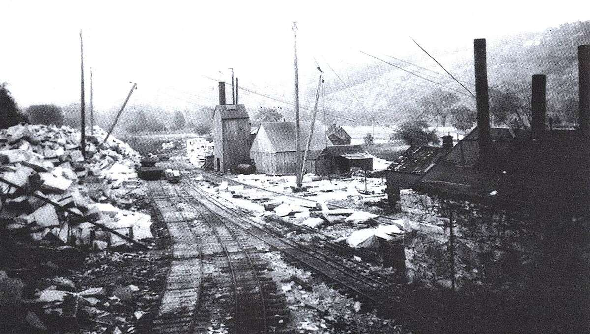 Stoneworkers in 1905 walked across the Shepaug River on a suspension bridge to reach the Rockside Quarry at Mine Hill in Roxbury. This photo by Joseph West shows cut granite, ready to be hauled down the mountainside on narrow-gauge rails, where it was shipped to Bridgeport, New York City or other locations. Before the Shepaug Valley Railroad opened in 1871, ox carts provided the means of transportation for the rocks.