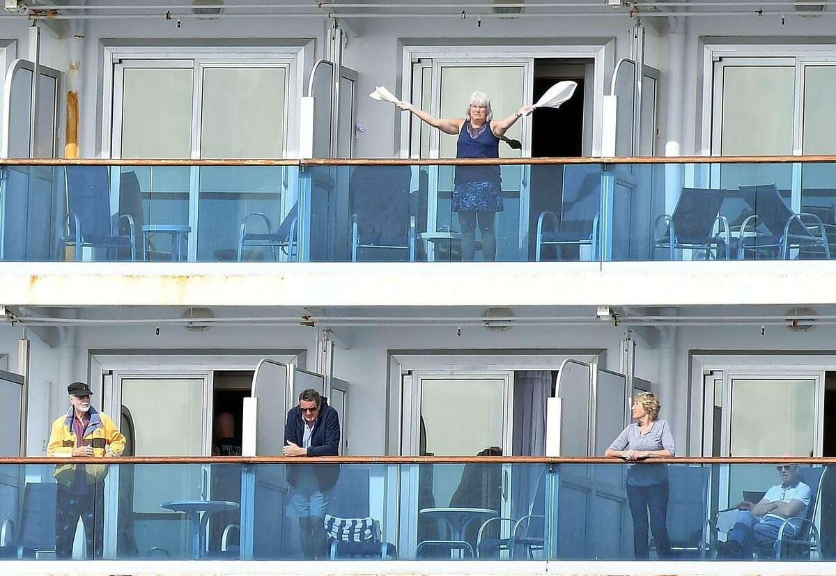(FILES) In this file photo taken on March 08, 2020 a woman gestures as other people look on from aboard the Grand Princess cruise ship, operated by Princess Cruises, as it maintains a holding pattern about 25 miles off the coast of San Francisco, California. - The United States has now recorded more than 100,000 coronavirus-related deaths, Johns Hopkins University reported Wednesday -- a somber milestone and by far the highest total in the world. The country reported its first death about three months ago. Since then, nearly 1.7 million infections have been tallied nationwide, according to the Baltimore-based school. The actual number of deaths and infections is believed to be higher, experts say. (Photo by Josh Edelson / AFP) / Alternative Crop (Photo by JOSH EDELSON/AFP via Getty Images)