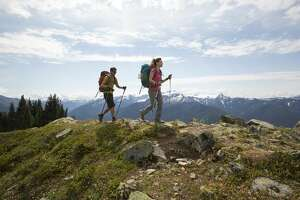 A young couple backpacking along a trail in the Olympic National Park.