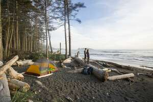 A couple watching sunset while backpacking along the coast in the Olympic National Park.