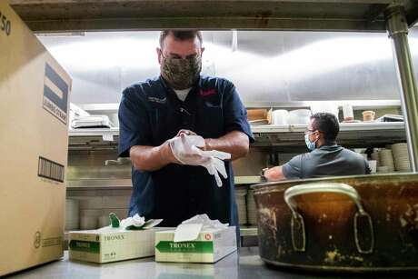 Molina's Cantina owner Ricardo Molina puts on gloves while wearing a protective mask to handle take-out food at his restaurant on Friday, May 29, 2020, in Houston. Molina who owns two restaurants has been taking precautions to ensure his guests feel safe ordering take-out or visiting the establishment.