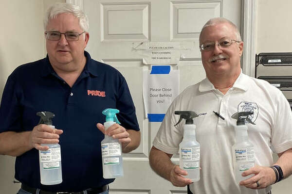Jim Seubert, left, stands holding his product (Hydrolyze Disinfectant Spray) with one of his customers, New Hanover County Fire and Rescue deputy fire chief, Frank Meyer. New Hanover County encompasses Wilmington, North Carolina where Seubert has his second Pride Restoration location.