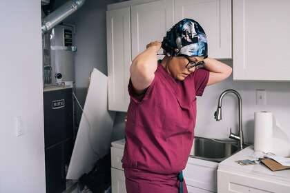 Dr. Debbie Madhok, an emergency room physician at Zuckerberg San Francisco General Hospital and Trauma Center, puts on a surgical cap in a makeshift decontamination station in her garage before going to work.