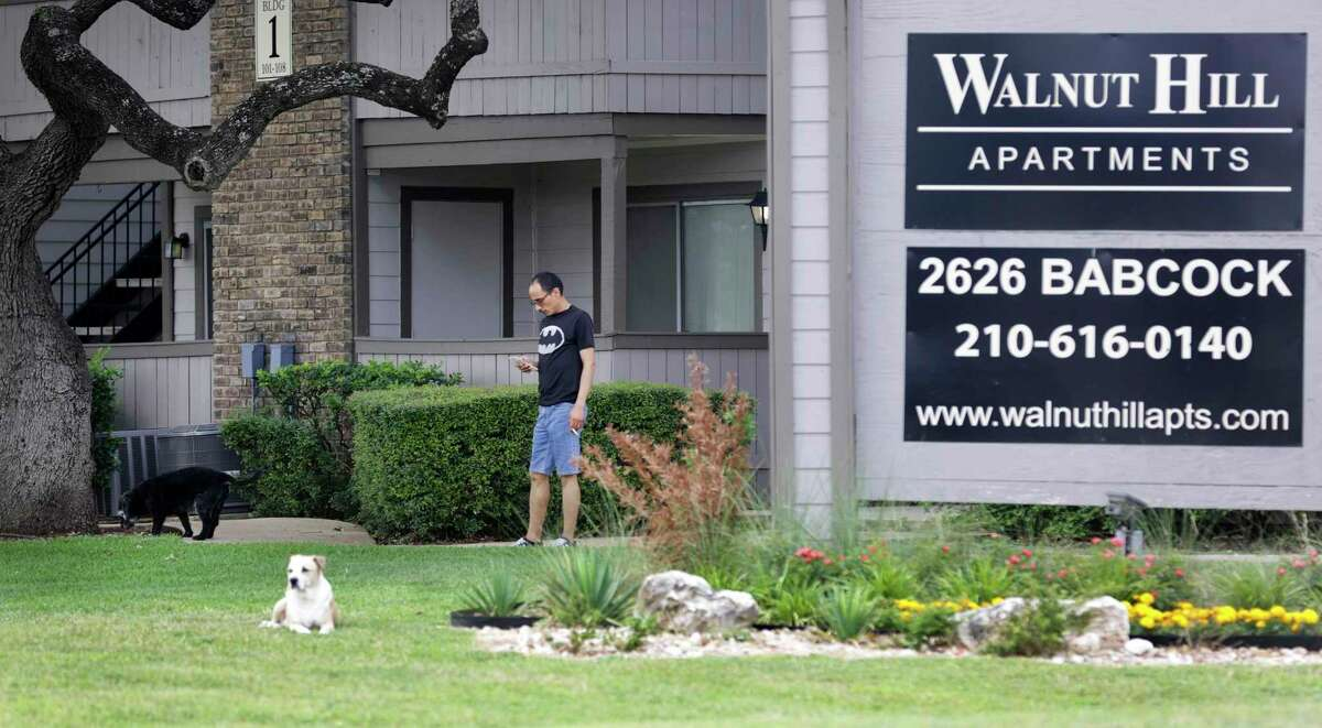 Two months into the pandemic, renters as well as landlords are still facing issues, on Friday, May 22, 2020. A man walks his dogs in front of Walnut Hill Apartments.