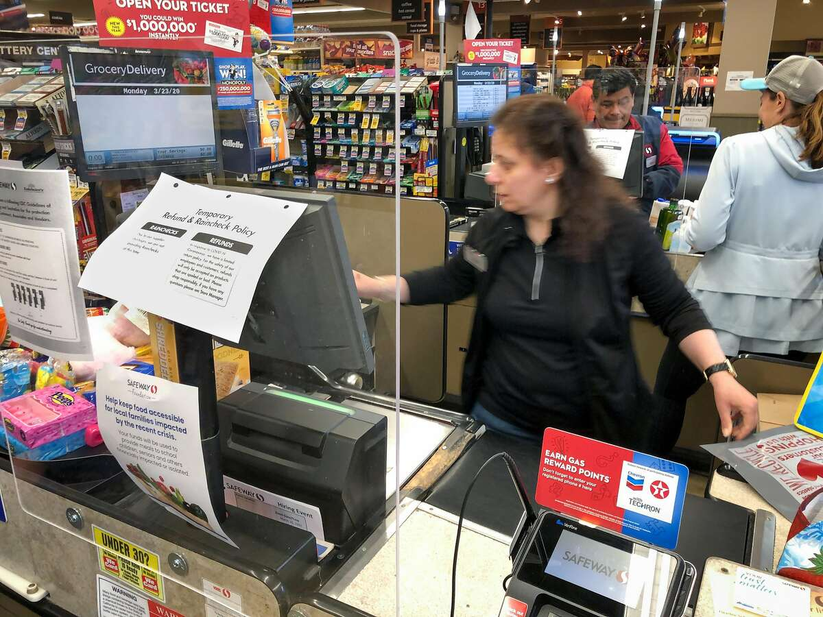 New plexiglass screens keep checkers and customers more safe from the spread of coronavirus at the Crystal Springs Village Safeway Monday, March 23, 2020, in San Mateo, Calif.