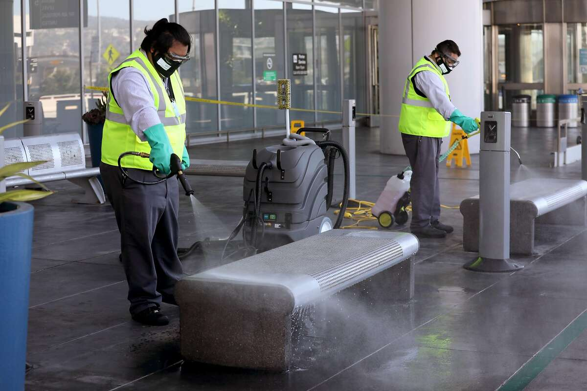 San Francisco International airport custodial staff Brian Orencia (left) and Juan Ramos (right) disinfect curbside departure seating area at the SFO International terminal seen on Tuesday, May 26, 2020, in San Francisco, Calif.