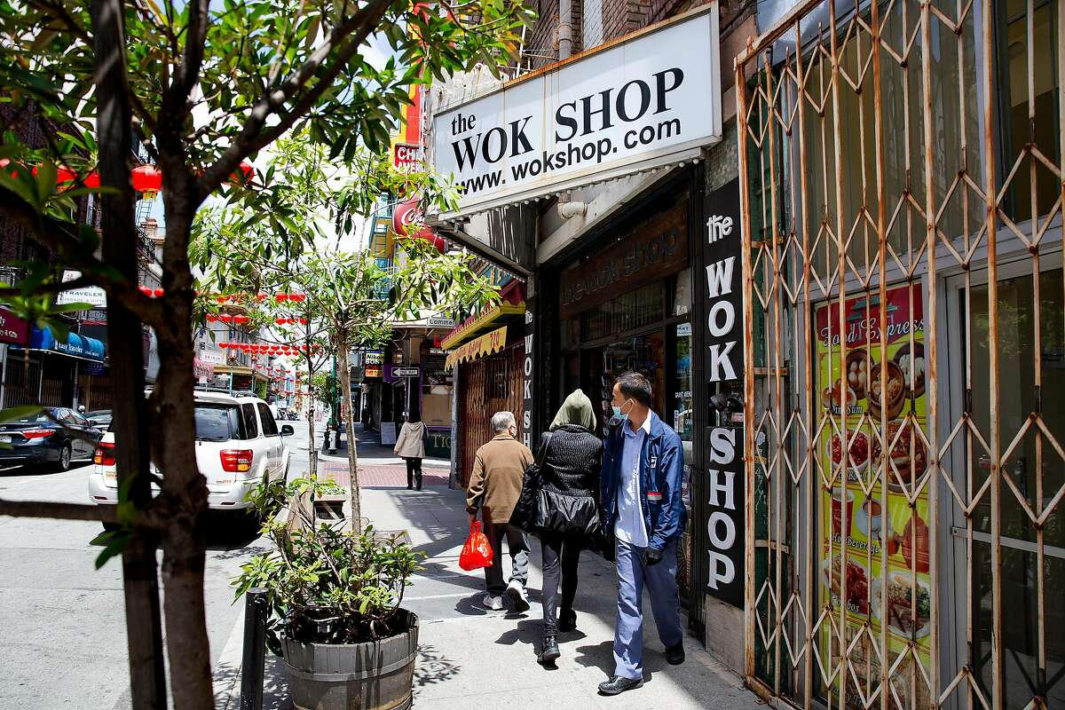 People walk by the currently open Wok Shop in China Town in San Francisco, Calif. on Friday, May 29, 2020. Thanks to online sales, Tane Chan has been able to keep her shop open and running during the Shelter-In-Place orders. Chan worries what will happen to other small businesses who have not been able to maintain income through e-commerce and online sales.