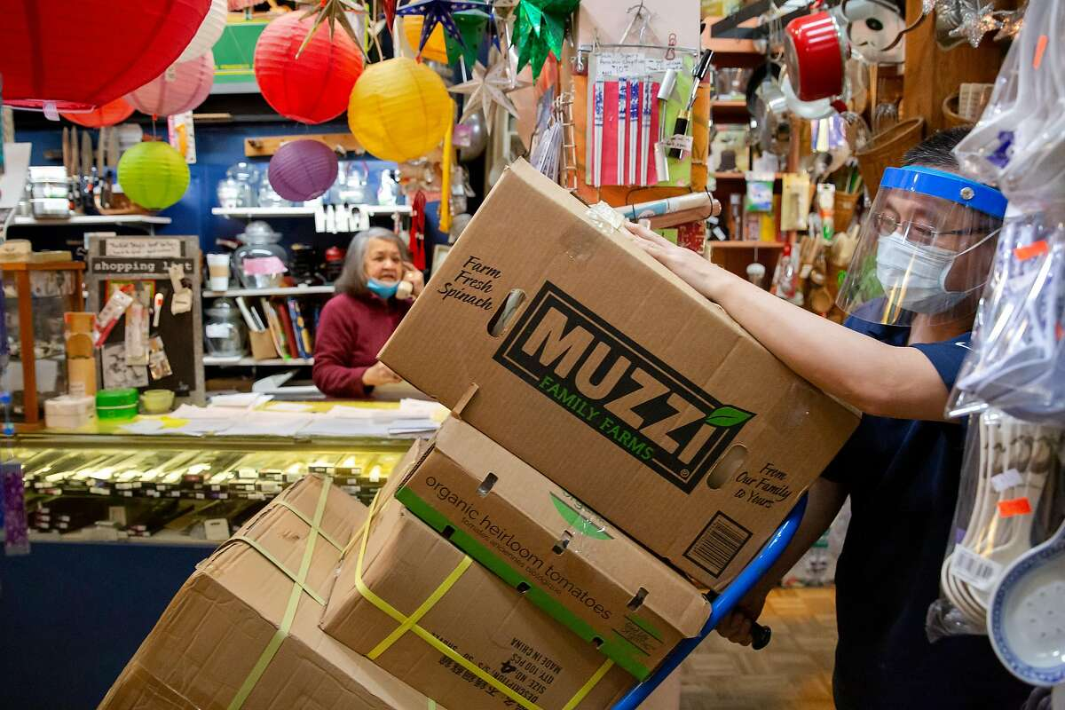 A delivery person brings in boxes of merchandise at the Wok Shop in China Town in San Francisco, Calif. on Friday, May 29, 2020. Thanks to online sales, Tane Chan has been able to keep her shop open and running during the Shelter-In-Place orders. Chan worries what will happen to other small businesses who have not been able to maintain income through e-commerce and online sales.