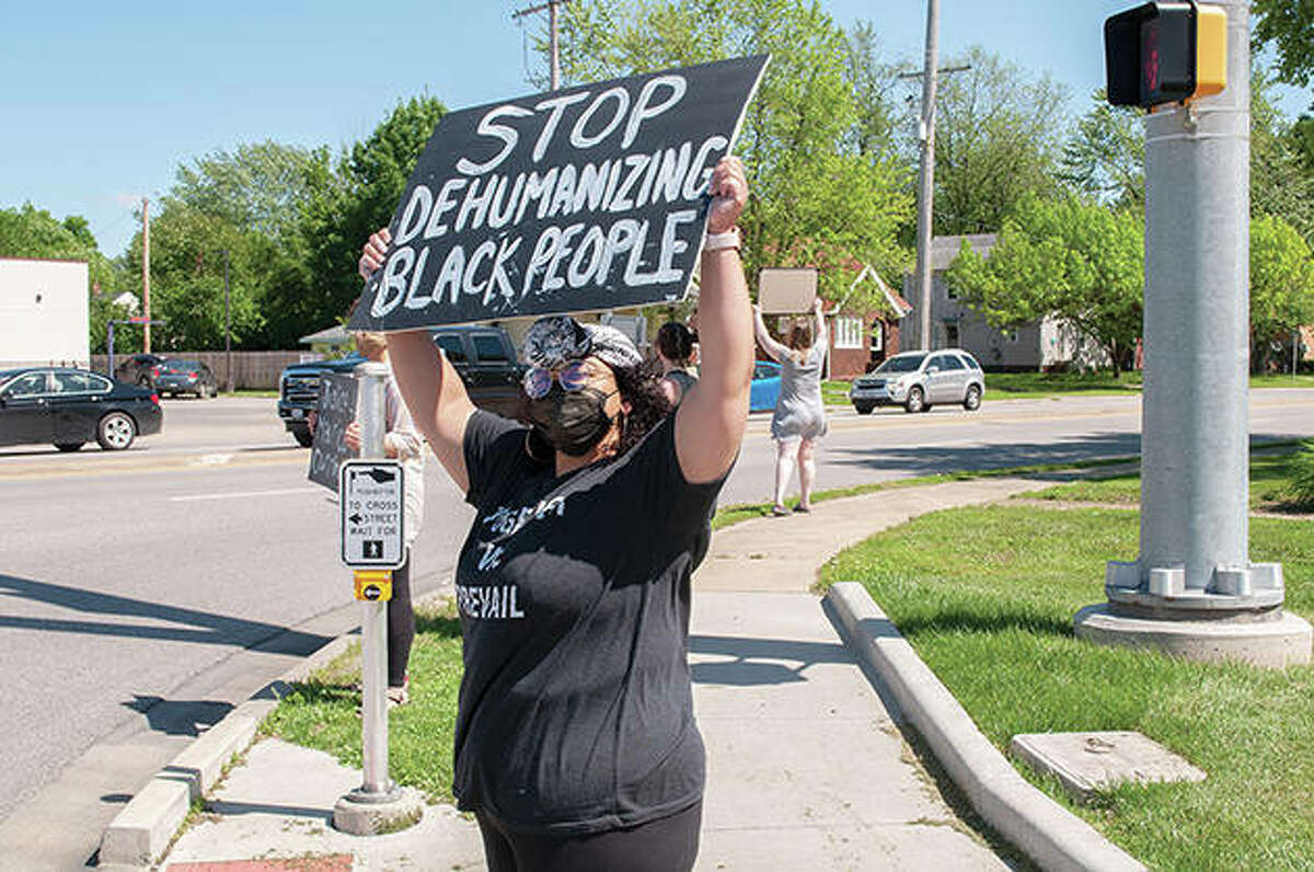 """Protesters gather Friday on Morton Avenue in Jacksonville, holding signs to protest the death of George Floyd in Minneapolis. Seirra Helmer, whose sign reads """"Stop dehumanizing black people,"""" organized the rally. """"I can at least stand here and hold a sign,"""" Helmer said. """"They (police) knew they were being videoed and they still killed him."""" Floyd, a 46-year-old black man, died Monday while being detained by Minneapolis police officers. Videos show Floyd pleading for air and saying he can't breathe as a white officer uses a knee restraint on Floyd's neck."""