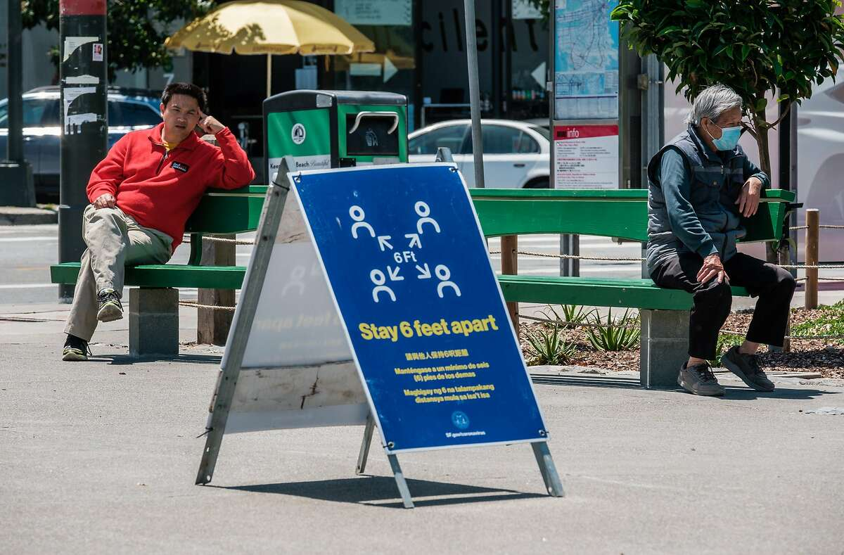 People sit on park benches near a public health sign encouraging social distancing in Washington Square in San Francisco on Thursday, May 21, 2020.