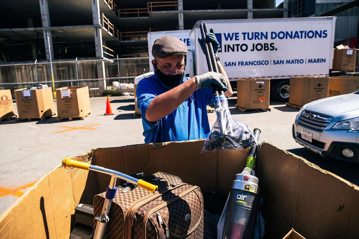 Ricardo Landecho organizes a pallet of donated goods at the Goodwill no-contact drop-off donation site on Thursday, May 28, 2020 in San Francisco, California.
