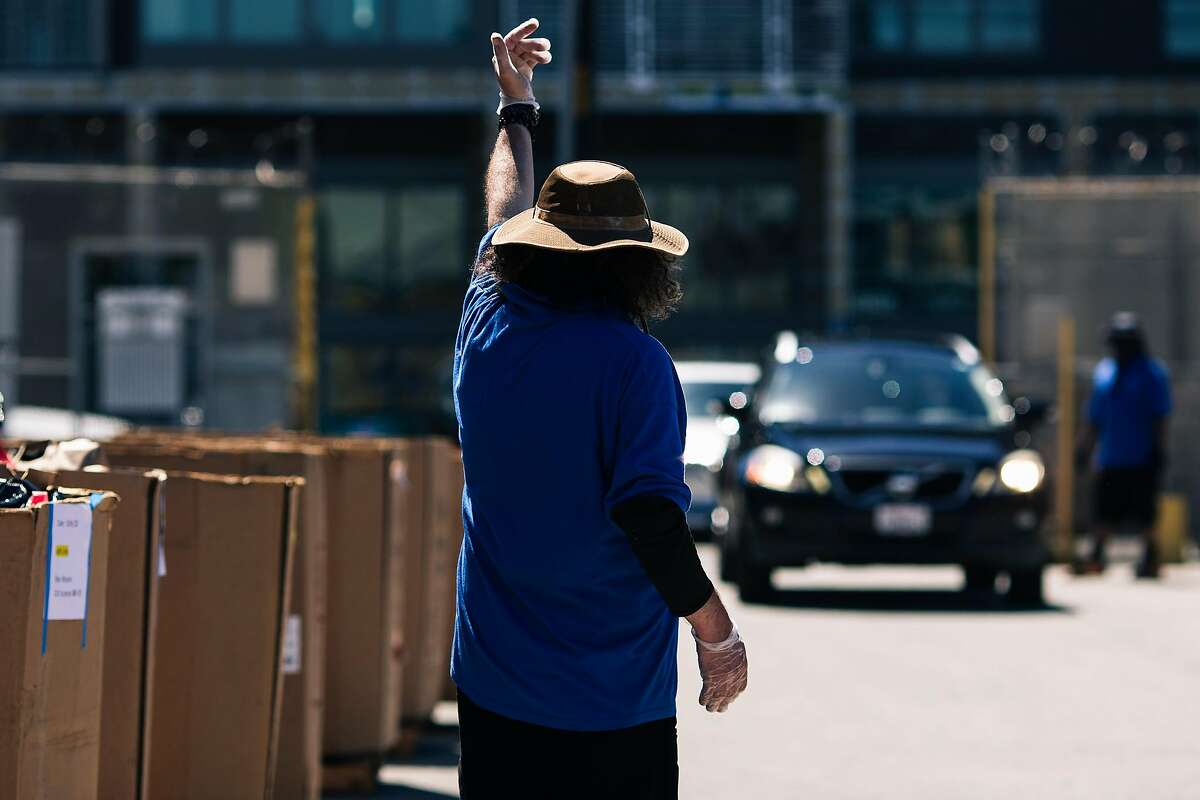 A worker directs a vehicle at the Goodwill no-contact drop-off donation site on Thursday, May 28, 2020 in San Francisco, California.