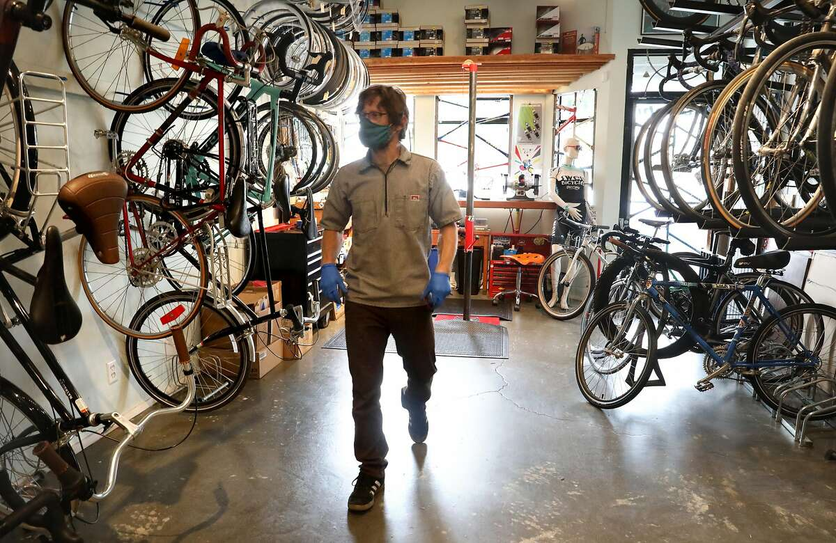 Bike shop owner and essential worker Uri Friedman (middle) repairs bicycles to get them back on road during pandemic at Swell Bicycles on Thursday, May 28, 2020, in San Francisco, Calif.