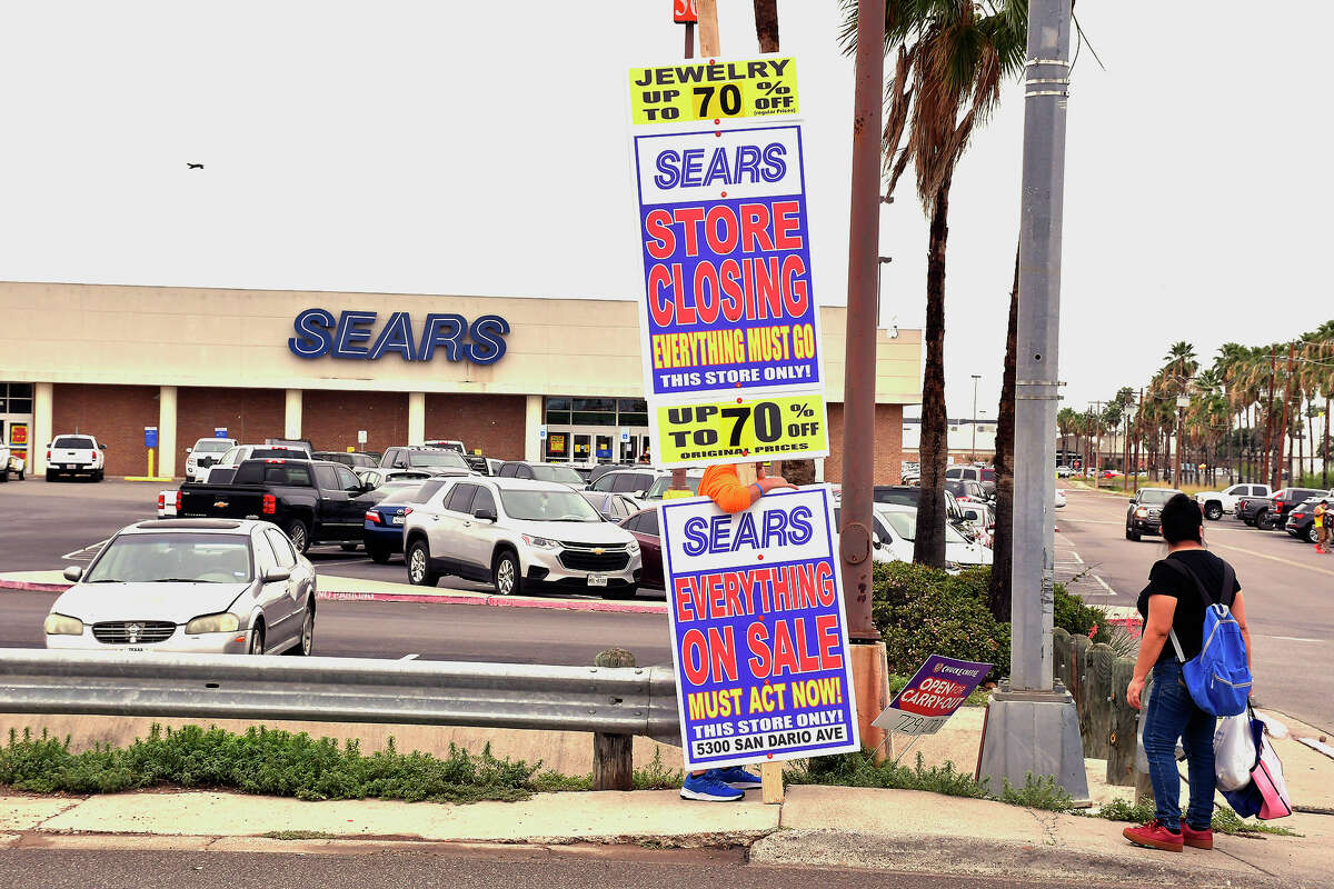 A man carries a sign advertising the closing of the SEARS Store at Mall del Norte, Friday, May 29, 2020, customers were seen entering and leaving the store as they checked for markdown prices on items.
