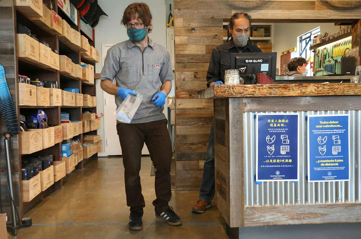 Bike shop owner and essential worker Uri Friedman (left) and general manager Ron Manansala working at Swell Bicycles on Thursday, May 28, 2020, in San Francisco, Calif.